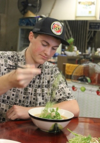 Eli mastering chop sticks while eating a delicous pho noodle soup.